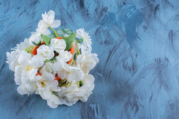 Bouquet von blassen blumen in einer orangefarbenen vase auf blau.