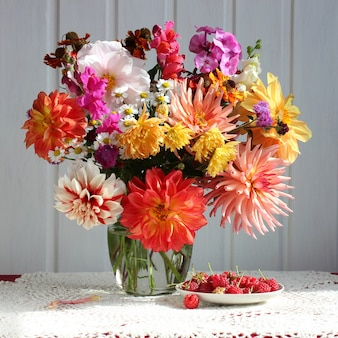 Bouquet von dahlien und himbeeren auf dem tisch mit spitze