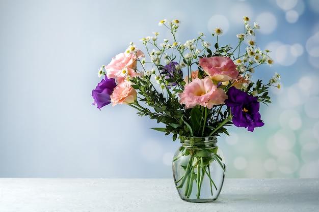 Bouquet von eustoma mit buchsbaum und kleinblättrigen zweigen auf einem tisch auf blauem hintergrund