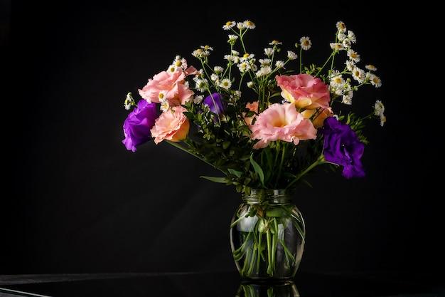 Bouquet von eustoma mit buchsbaum und kleinblättrigen zweigen auf einem tisch auf schwarzem hintergrund