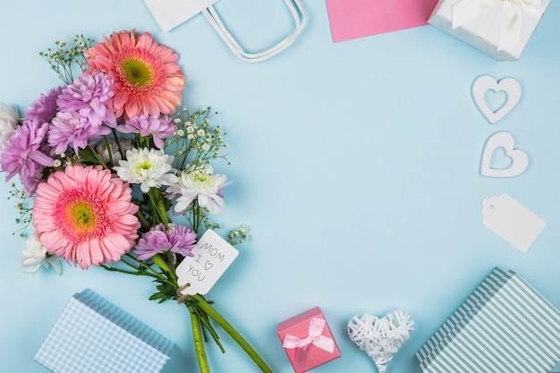 Bouquet von frischen blumen mit titel auf tag in der nähe von paket, geschenkkartons und dekorationen