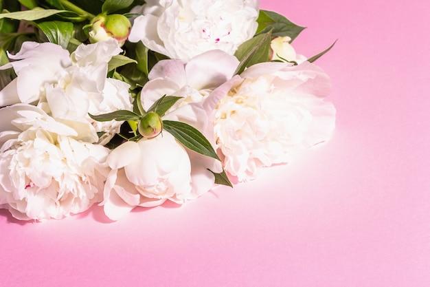 Bouquet von frischen weißen pfingstrosen. zarte sommerblumen, romantisches geschenkkonzept. blumenarrangement, trendiges hartes licht, dunkle schatten. betonhintergrund aus schwarzem stein, platz für text