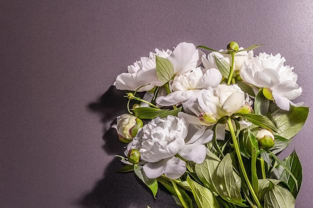 Bouquet von frischen weißen pfingstrosen. zarte sommerblumen, romantisches geschenkkonzept. blumenarrangement, trendiges hartes licht, dunkle schatten. betonhintergrund aus schwarzem stein