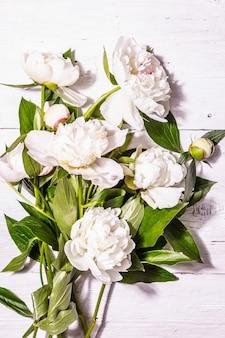 Bouquet von frischen weißen pfingstrosen. zarte sommerblumen, romantisches geschenkkonzept. blumenarrangement, trendiges hartes licht, dunkle schatten. weißer alter plankenhintergrund, draufsicht