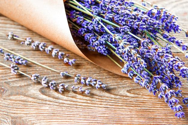 Bouquet von getrocknetem lavendel in kraftpapier auf hölzernem hintergrund