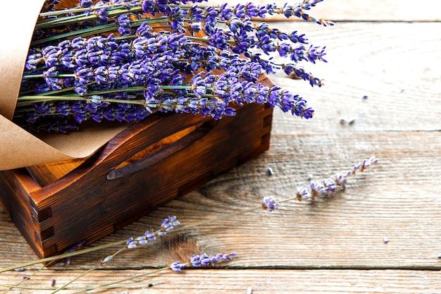 Bouquet von getrocknetem lavendel in kraftpapier in einer holzkiste