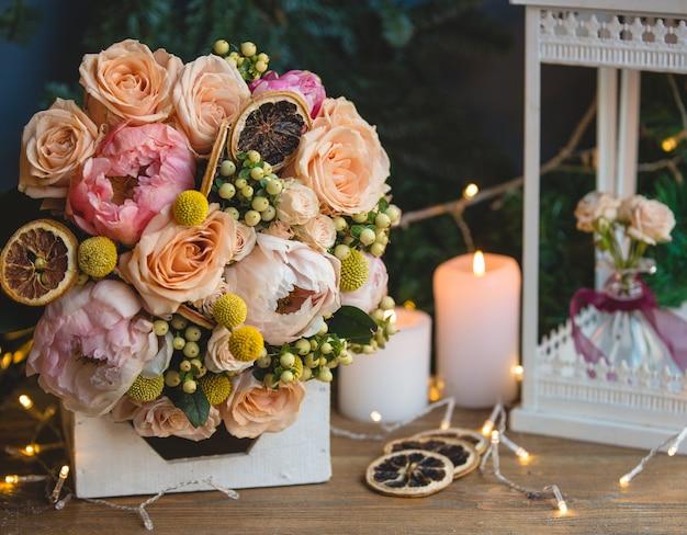 Bouquet von holly beeren, pfingstrosen und trockenen zitronenscheiben.