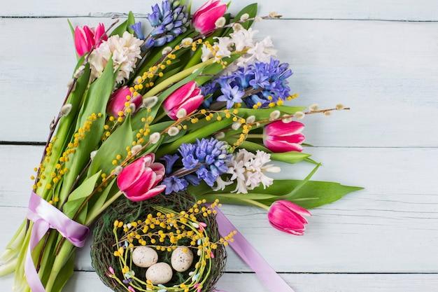 Bouquet von hyazinthen, mimosen, weiden, tulpen und ostereiern in einem nest auf einem hellen hölzernen hintergrund