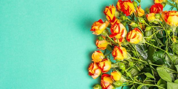 Bouquet von leuchtend orangefarbenen rosen auf türkisfarbenem hintergrund