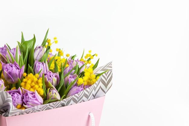 Bouquet von lila tulpen und gelben mimosen in rosa box auf weiß