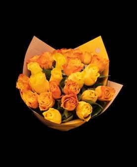 Bouquet von orangefarbenen rosen in festlicher verpackung auf schwarzem hintergrund isoliert. foto in hoher qualität