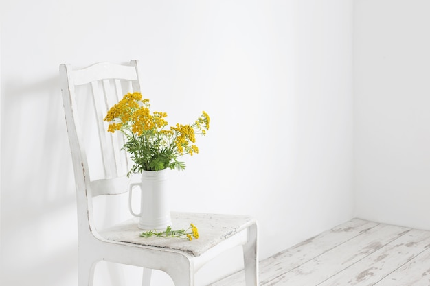 Bouquet von rainfarn auf altem holzstuhl in weißem interieur