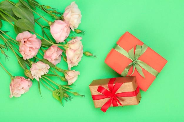 Bouquet von rosa blumen mit blättern und geschenkboxen mit band auf grünem hintergrund gebunden. ansicht von oben. konzept zum feiertag.