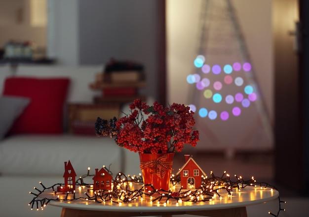 Bouquet von roten beeren mit heller girlande auf einem tisch