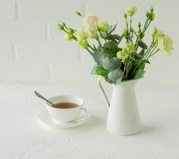 Bouquet von schönen eustoma-blumen auf dem tisch im esszimmer. innenarchitektur. kaffeepause.