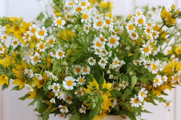 Bouquet von weißen und gelben blumen, lysimachia und kamille nahaufnahme, selektiver fokus.