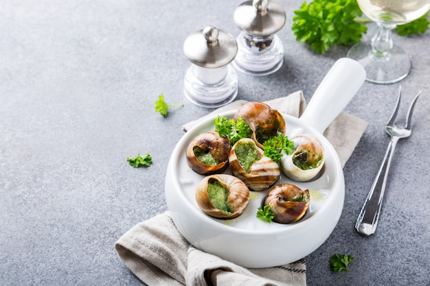 Bourgogne escargot snails mit knoblauchkräuterbutter in weißer pfanne