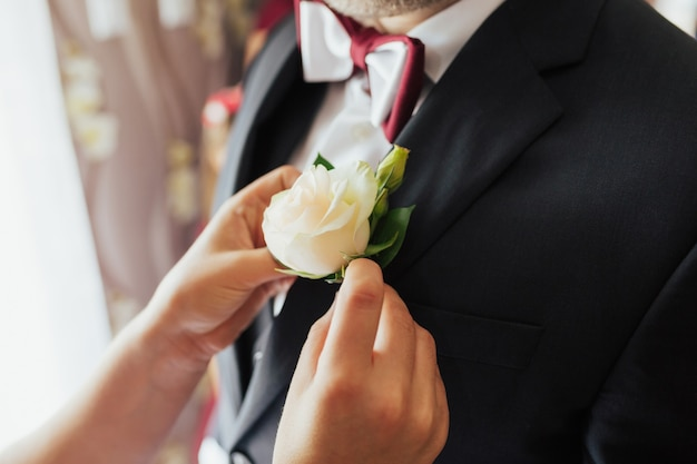 Boutonniere aus weißer rose auf der hochzeitsjacke des bräutigams