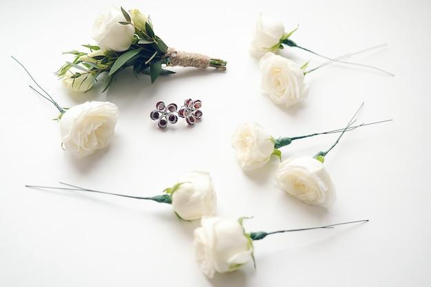 Boutonniere des bräutigams aus weißen rosen und grünen blättern. nahe blumen und ohrringen der braut. hochzeitsutensilien und zubehör.