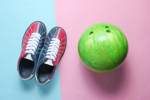 Bowlingschuhe und bowlingkugel auf einem rosa-blauen pastell.