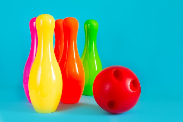 Bowlingspiel und ball für das spielen im bowlingspiel der kinder auf einem blauen hintergrund mit kopienraum