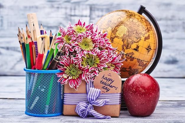 Box, blumen, globus und briefpapier. geschenk zum lehrertag.