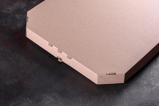 Box für die lieferung von köstlicher italienischer pizza auf dem dunklen tisch des italienischen restaurants