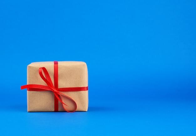 Box in braunes papier gewickelt und mit einer roten schleife gebunden, geschenk auf blau