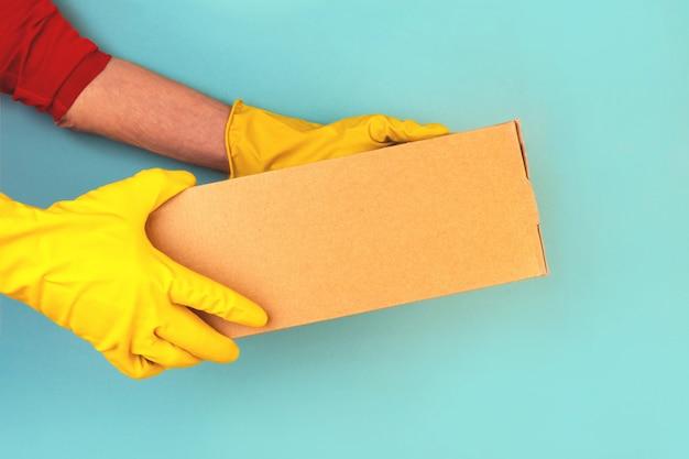 Box mit bestellten waren in den händen eines kuriers. gummihandschuhe, kontaktlose lieferung. quarantäne, selbstisolation.