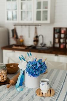Box mit blumen und einer tasse auf dem tisch