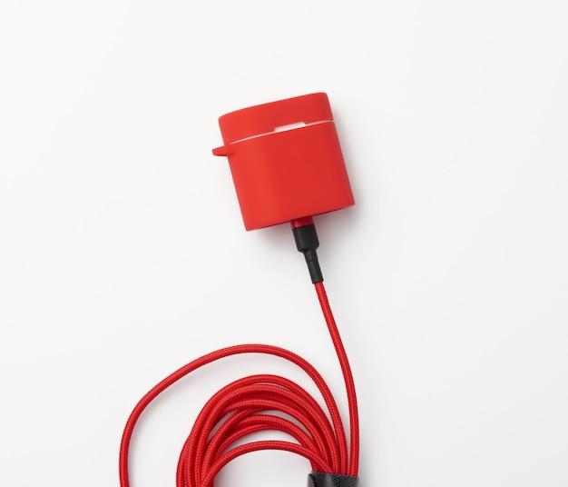 Box mit einem kopfhörer-ladegerät in einer roten hülle, die auf einer weißen oberfläche am kabel befestigt ist