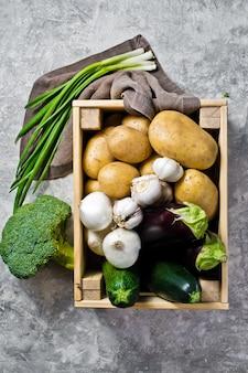 Box mit gemüse: kartoffeln, zwiebeln, knoblauch, auberginen, zucchini, brokkoli, frühlingszwiebeln. bauernhof.