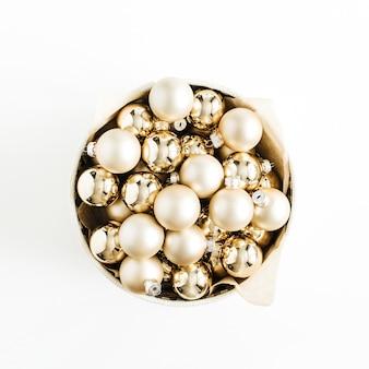 Box mit goldenen weihnachtsdekorationskugeln auf weißer oberfläche. draufsicht