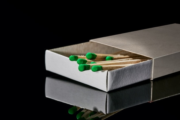 Box mit grünen streichhölzern lokalisiert auf einem schwarzen hintergrund