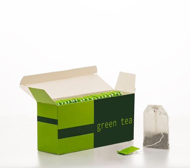 Box mit grünen teebeuteln lokalisiert auf weiß