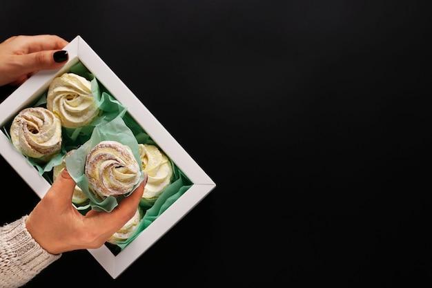 Box mit hausgemachten marshmallows in weiblichen händen auf dunklem hintergrund, horizontale ausrichtung, draufsicht, textfreiraum