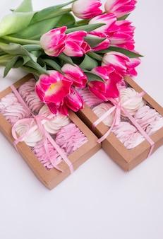 Box mit hausgemachten marshmallows und einem strauß tulpen