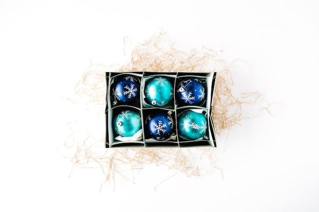 Box mit hellblauen weihnachtskugeln auf weiß
