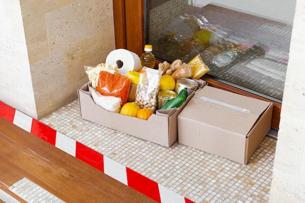 Box mit lebensmitteln während der selbstisolierung in der quarantäne zu hause. food box lieferung vor der haustür in der nähe der tür hinter der linie. kontaktlose lieferung, sicheres einkaufen. soziales distanzkonzept