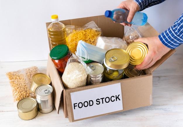 Box mit lebensmittelvorrat. karton mit butter, konserven, müsli und nudeln. reservieren.