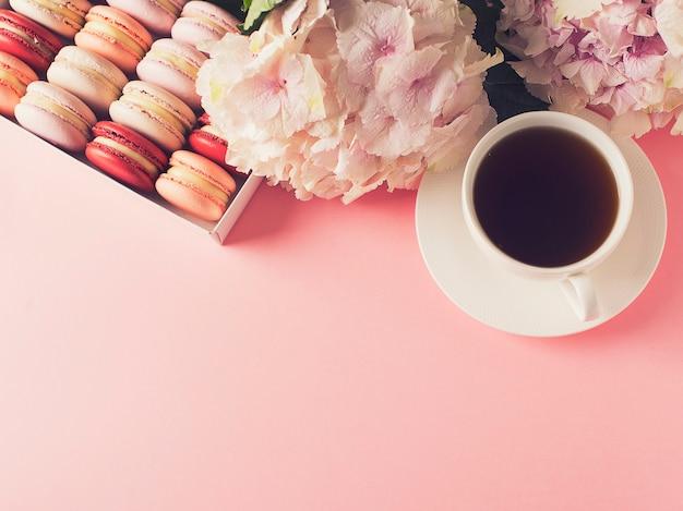 Box mit makronen und tasse kaffee, blumen auf rosa