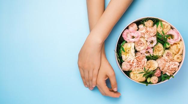 Box mit schönen blumen neben frauenhänden auf dem blauen hintergrund mit kopienraum. schönheit