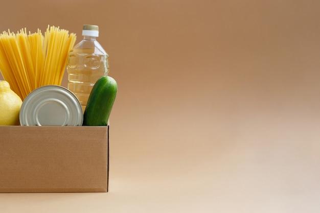 Box mit vorrat an lebensmitteln. spende von produkten für bedürftige. gemüse, dosen und nudeln