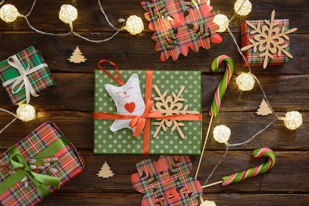 Box mit weihnachtsgeschenk verziert mit handgemachten spielzeugen der katze auf dem holztisch
