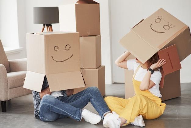 Boxen auf den köpfen. glückliches paar zusammen in ihrem neuen haus. konzeption des umzugs
