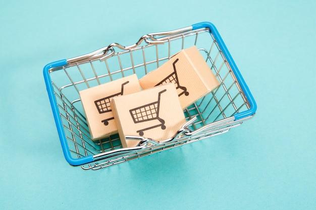 Boxen in einem einkaufskorb auf blau. einfaches einkaufen mit fingerspitzen für verbraucher