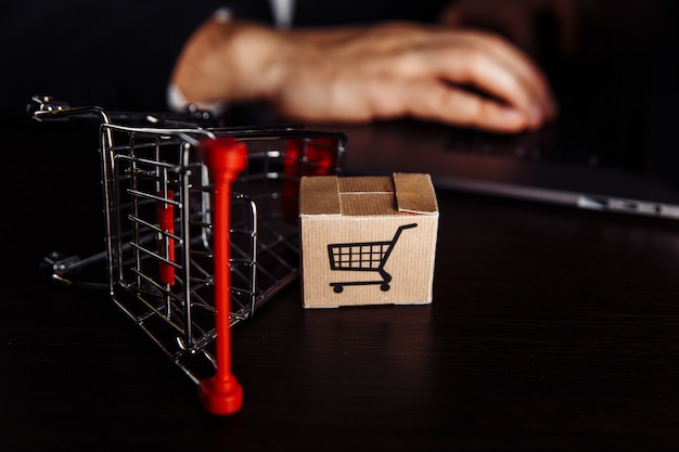 Boxen in einem wagen neben dem laptop. online-shopping-konzept