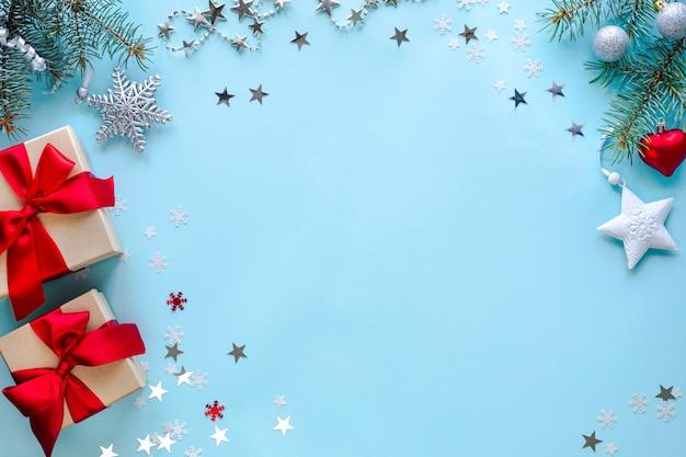 Boxen mit geschenken und weihnachtsdekorationen auf blauer oberfläche