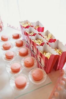 Boxen mit pop-mais stehen vor teller mit makronen