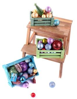 Boxen mit weihnachtsschmuck auf kleiner leiter, isoliert auf weiß